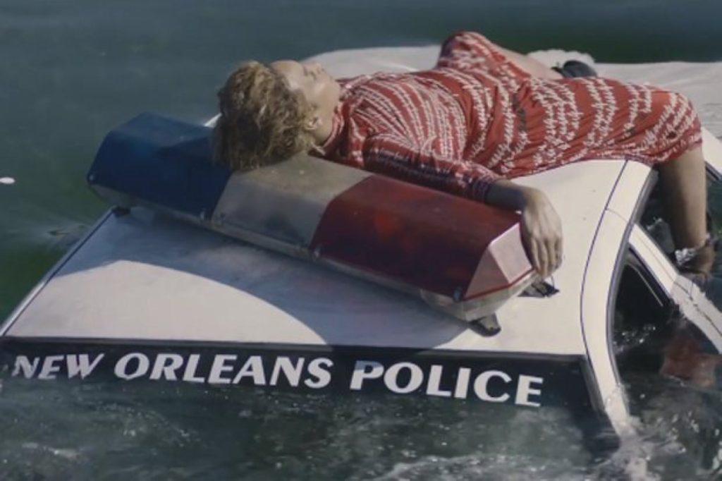 Beyoncé aparece sob uma viatura policial que, aos poucos, submerge nas águas do Katrina.